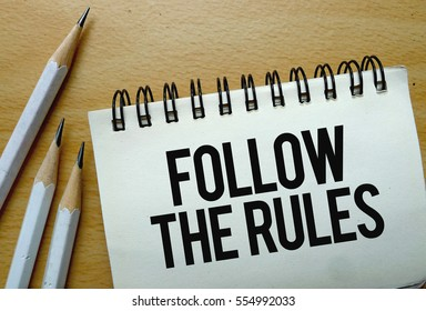 Follow The Rules text written on a notebook with pencils