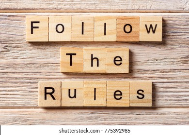 Follow The Rules word written on wood block. Follow The Rules text on table, concept.