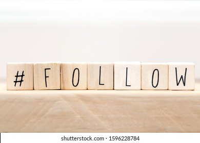 Follow sign made of cubes on a wooden table with Hashtag near white background, socialmedia concept close-up
