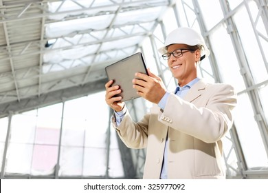 Follow the technologies. Low angle of upbeat positive professional architect holding laptop and using it while being busy at work