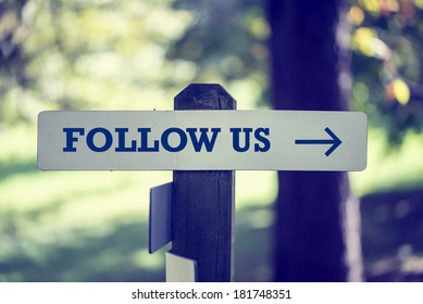 Follow Us signboard on a wooden post with a right pointing arrow outdoors against greenery in a faded retro image.