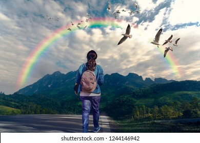 Follow your dream concept. A woman walking along the path to mountain and looking rainbow in the sky.