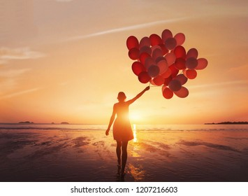 follow your dream, inspiration concept, silhouette of woman with colorful balloons on the beach