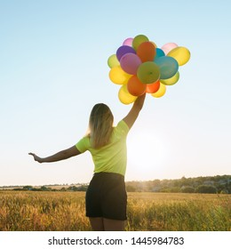 follow your dream, inspiration concept, young woman with colorful balloons in summer field. fun, vacation, bright life