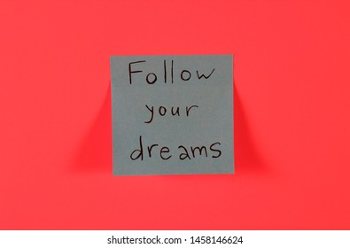 Follow your dreams. Blue sticky note with inspirational quote on neon pink background. Handwritten positive reminder/advice. Concept for confidence, courage and motivation. Sign of moral support.