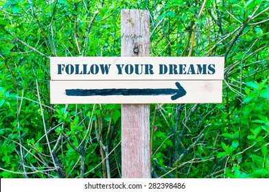 FOLLOW YOUR DREAMS written on Directional wooden sign with arrow pointing to the right against green leaves background. Concept image with available copy space
