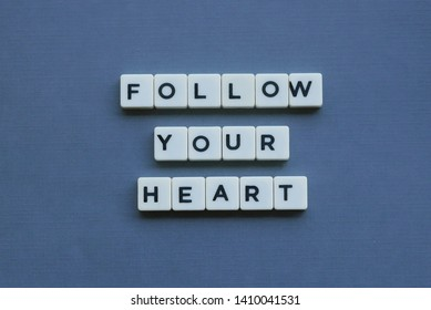 ' Follow Your Heart ' word made of square letter word on grey background.