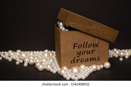 Follow yur dreams wooden box filled up and surrounded with the white pearls on the black background.