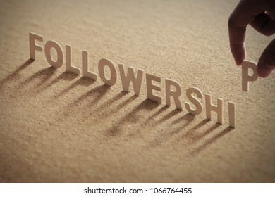 FOLLOWERSHIP wood word on compressed or corkboard with human's finger at P letter.