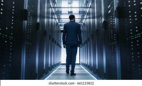 Following Shot of IT Engineer Walking Through Data Center with Rows of Working Rack Servers on Both Sides.