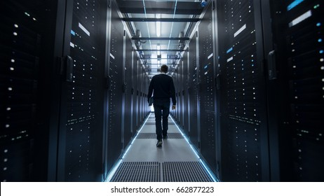 Following Shot of IT Engineer Walking Through Data Center Corridor with Rows of Rack Servers.