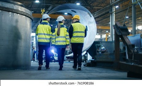 Following Shot of Three Engineers Walking Through Heavy Industry Manufacturing Factory. In the Background Welding Work in Progress, Various Metalwork, Pipeline/ Barrel Components.