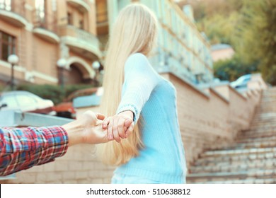 Follow-me concept. Young woman holding man's hand on street stairs background