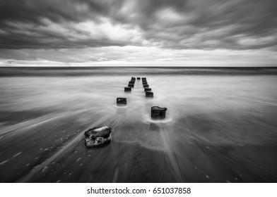 Folly Beach Charleston South Carolina Long Exposure Black and White Seascape photography featuring moving ocean water around old wooden poles