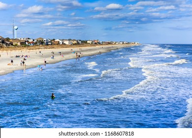 """FOLLY BEACH, SC/USA - MARCH 30, 2015:  Residents and tourists flock to the Atlantic Ocean at Folly Beach, also known as the """"edge of America,"""" near Charleston in South Carolina."""