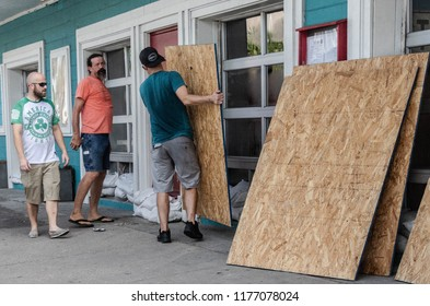 Folly Beach, South Carolina/United  States - Sept. 11, 2018: Workers board windows at a restaurant in preparation for Hurricane Florence.