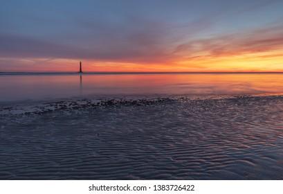 Folly Beach at sunrise with the Morris Island Lighthouse in the distance near Charleston, South Carolina.
