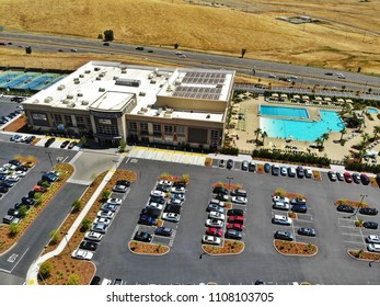 FOLSOM, CA, USA - June 2, 2018: Aerial drone view of Life Time Fitness Gym and outside parking lot, pools, tennis court on sunny summer day.