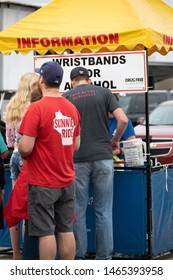 Fond du Lac, Wisconsin / USA - July 20, 2019 : Fair Attendees Waiting in Line at the Information Booth to get a Wristband to Prove Age for Alchohol Purchase