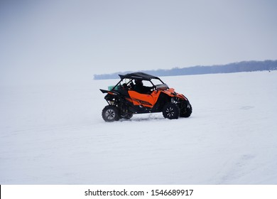 Fond du Lac, Wisconsin / USA - March   9th, 2019: Adult girls having fun driving a 2017 Yamaha YXZ1000R SS SE on the ice of the frozen lake of Winnebago in Fond du Lac, Wisconsin