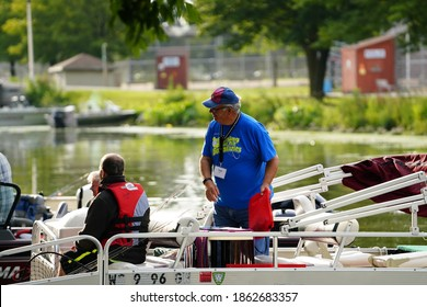 Fond du Lac, Wisconsin USA - August 25th, 2020: Fishermen boating and on the river in lakeside park in fond du lac