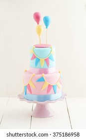 Fondant covered pastels coloured birthday cake with buntings and balloons