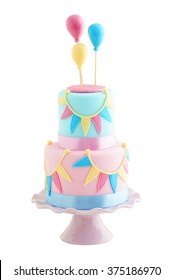 Fondant covered pastels coloured birthday cake with buntings and balloons iolated on white