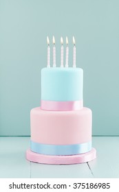 Fondant covered pastels coloured birthday cake with five birthday candles