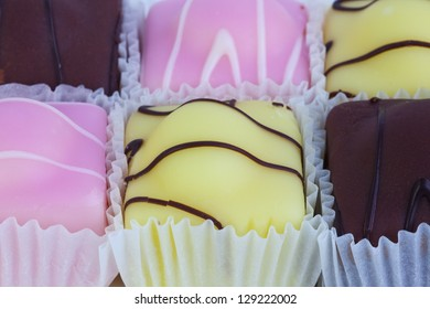 Fondant fancies - small individual iced cakes close-up.