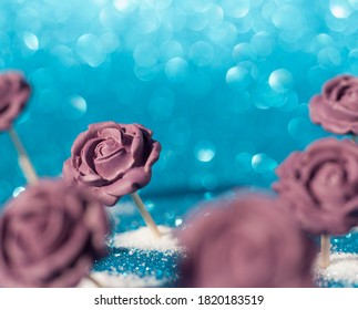Fondant lilac roses on sparkling glitter background. Comestible flowers. Pastry craft.