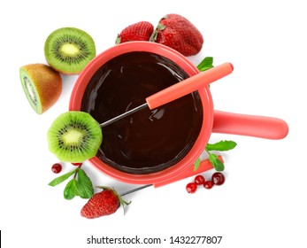 Fondue pot with dark chocolate, fruits and berries on white background, top view