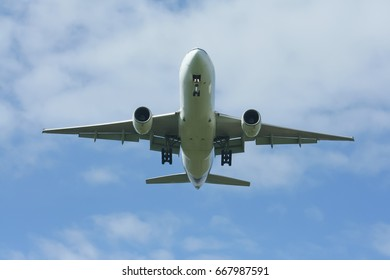 Font view Passenger Airplane Landing with cloud and blue sky