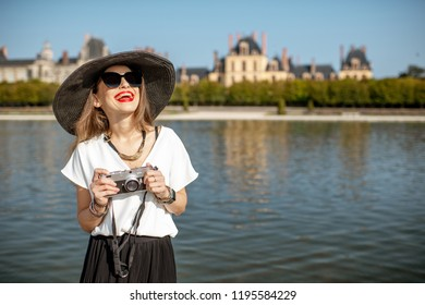 FONTAINBLEAU, FRANCE - August 28, 2017: Portrait of a young woman tourist standing with photocamera in Fontainebleau gardens with palace on the background, France