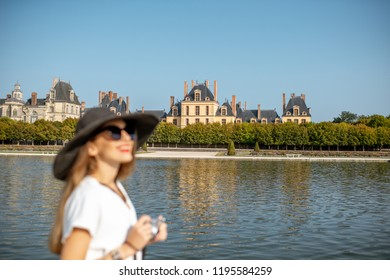 FONTAINBLEAU, FRANCE - August 28, 2017: Portrait of a young woman tourist standing with photocamera in Fontainebleau gardens with palace on the background, France. Woman is out of focus