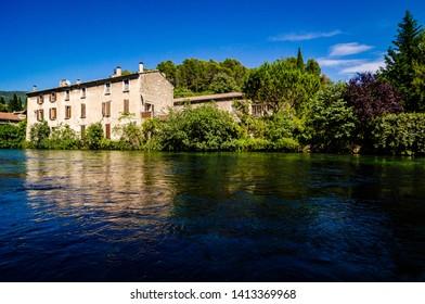 Fontaine de Vaucluse, France - June 16, 2018. Stone house by the clear river Sorgue