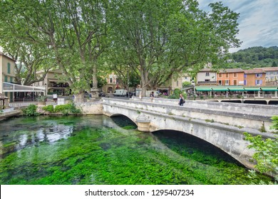 Fontaine de Vaucluse, Provence, Luberon, Vaucluse/France - 05 31 2017: Young smiling Women walking across the bridge at the river Sorgue