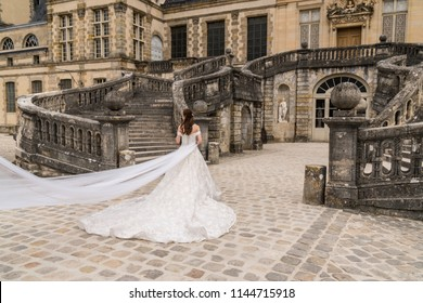 Fontainebleau, France - June 18, 2018: Bride in white dress having wedding bridal photos taken at Chateau Fontainebleau in France.