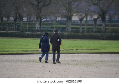 FONTAINEBLEAU, PARIS/FRANCE - DECEMBER 2017: Old couple walking and crossing Fontainebleau Garden, man with hat walking and taking a baguette under the arm. Fontainebleau, Paris/France.