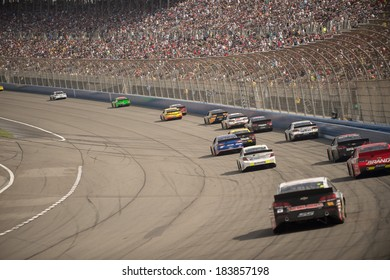 FONTANA, CA - MAR 23: Race cars going down the frontstrech at the Nascar Sprint Cup Auto Club 400 race at Auto Club Speedway in Fontana, CA on March 23, 2014