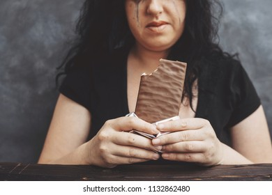 Food addiction, dieting concept. Young overweight woman fed up with diets eating chocolate greedily and crying