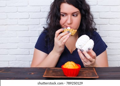 Food addiction, dieting concept. Young overweight woman fed up with diets eating a cake.