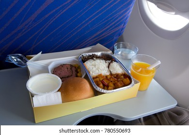 Food in airplane. On board meal set on the tray. Meat appetizer, butter, bread, yoghurt. Hot dish in the aluminum lunch box: chicken, rice and vegetables. Drink: orange juice and water.