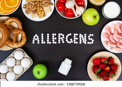 Food allergens as milk, oranges, tomatoes, garlic, shrimp, peanuts, eggs, apples, bread, strawberries on wooden table.