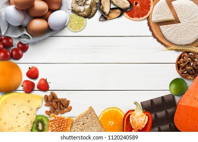 Food allergy collage. Set of allergic products, cheese, honey, citrus fruits, eggs, chocolate, berries and seafood on wooden boards, isolated on white wood, top view, cooy space