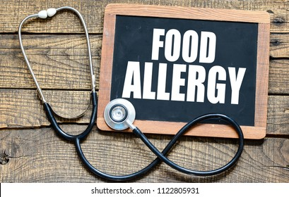 FOOD ALLERGY handwritten with white chalk on a blackboard on wood background
