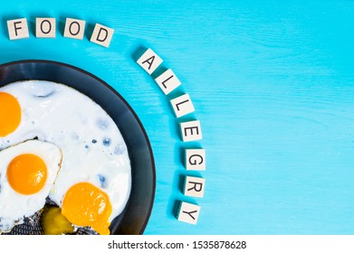 food allergy. word made of wooden blocks on a wooden background, scrambled eggs in a frying pan place for text