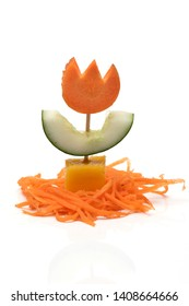 Food art creative concept. Cute flower made of carrot, mango, cucumber over white background. Vegetable and fruit flower.