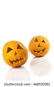 Food art creative concept. Halloween scary faces carved into yellow orange fruit isolated  over a white background.