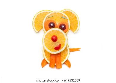 Food art creative concepts. Cute puppy dog made of fruits and vegetables such as orange, banana and carrots isolated over white background.