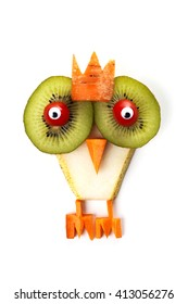 Food art creative concepts. Funny owl (bird) made of pear, kiwi, tomatoes and carrots isolated on a white background.